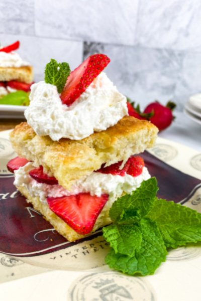 strawberry-shortcake-with-sweet-biscuits-and-whipped-cream-my-home-and-travels- served on a plate with mint featured image