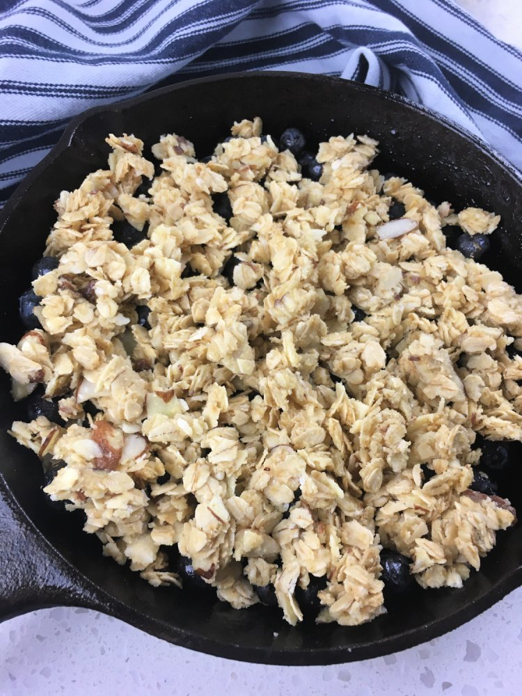 Simple Blueberry Crisp with Maple Syrup my home and travels image blueberry mixture poured into skillet adding topping